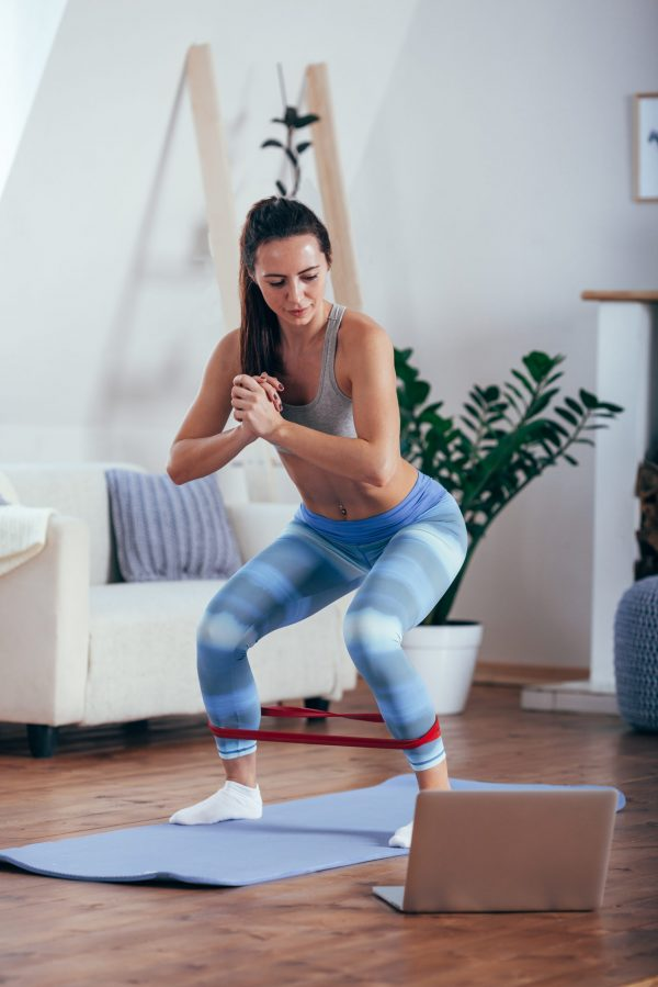 Sporty athletic woman exercising with red rubber tape at home and looking to the laptop
