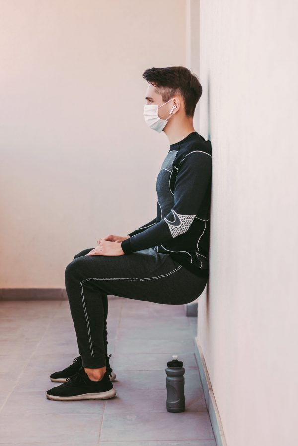 Confident sports man in protective mask doing wall leg sit exercise on balcony. Young athletic man fitness instructor train workout at home. Man squatting at wall. Coronavirus COVID-19 home quarantine